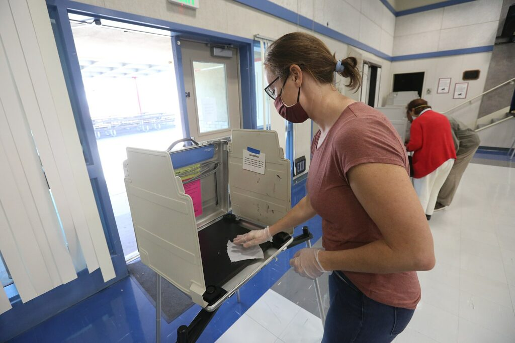 A California poll worker sanitizes a voting booth following its use at a Voter Assistance Center in Davis, CA during the 2020 General Election. Photo: Owen Yancher / Wikimedia